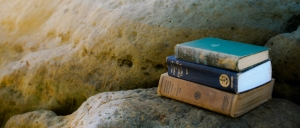 Books for an empowerment coach on rocks on the beach